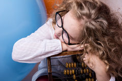 Muchacha adolescente rizada divertida, lista en vidrios con el ábaco de madera en t Fotografía de archivo
