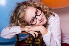 Muchacha adolescente rizada divertida, lista en vidrios con el ábaco de madera en t Fotografía de archivo libre de regalías