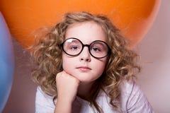 Muchacha adolescente rizada hermosa, elegante en vidrios en el fondo de Imagen de archivo libre de regalías