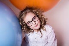 Muchacha adolescente rizada hermosa, elegante en vidrios en el fondo de Fotos de archivo libres de regalías