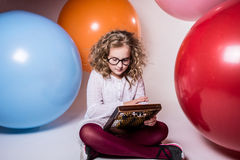 Muchacha adolescente rizada pensativa en vidrios con el ábaco de madera en Imagen de archivo libre de regalías