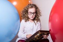 Muchacha adolescente rizada pensativa en vidrios con el ábaco de madera en Fotografía de archivo