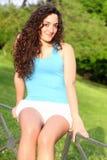 Muchacha adolescente rizada que sonríe en un parque Imagen de archivo