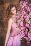 Muchacha adolescente rubia cerca de un árbol floreciente Imagen de archivo libre de regalías