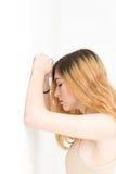 Muchacha adolescente rubia con los brazos que se inclinan en la pared pensativa y triste Fotografía de archivo