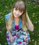 Muchacha adolescente rubia de la belleza con los ojos grandes que se sientan en hierba Imagenes de archivo