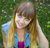 Muchacha adolescente rubia de la belleza con los ojos grandes que se sientan en hierba Fotografía de archivo