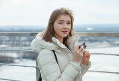 Muchacha adolescente rubia del estudiante adorable joven que charla con smartphone en la plataforma de observación con vistas al  Foto de archivo libre de regalías