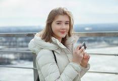 Muchacha adolescente rubia del estudiante adorable joven que charla con smartphone en la plataforma de observación con vistas al  Imágenes de archivo libres de regalías