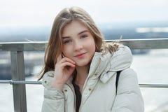 Muchacha adolescente rubia del estudiante adorable joven que se divierte que toca su barbilla en la plataforma de observación con Fotos de archivo libres de regalías