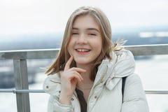 Muchacha adolescente rubia del estudiante adorable joven que se divierte que toca su barbilla en la plataforma de observación con Fotos de archivo