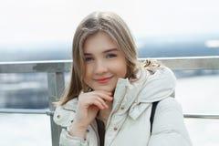Muchacha adolescente rubia del estudiante adorable joven que se divierte que toca su barbilla en la plataforma de observación con Foto de archivo libre de regalías