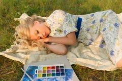 Muchacha adolescente rubia descalza encantadora hermosa cansada del pintor nosotros Foto de archivo