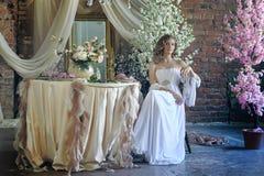 Muchacha adolescente rubia en un vestido blanco Foto de archivo libre de regalías
