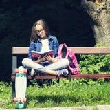 Muchacha adolescente rubia hermosa en camisa de los vaqueros que lee un libro en el banco con una mochila y un monopatín en el pa Fotografía de archivo libre de regalías