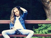 Muchacha adolescente rubia hermosa en camisa de los vaqueros, sentándose en banco con la mochila y el monopatín en parque Imagenes de archivo