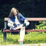 Muchacha adolescente rubia hermosa en camisa de los vaqueros, sentándose en banco con la mochila y el monopatín en parque Imágenes de archivo libres de regalías