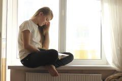 Muchacha adolescente rubia linda joven que se sienta en alféizar y que lee un libro Fotos de archivo
