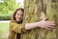 Muchacha adolescente rubia que abraza el tronco de árbol enorme Fotos de archivo libres de regalías