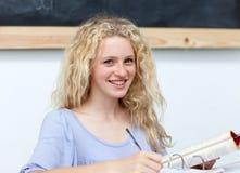 Muchacha adolescente rubia que estudia en la biblioteca Foto de archivo libre de regalías
