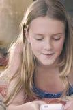 Muchacha adolescente rubia que manda un SMS en su teléfono Foto de archivo