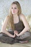 Muchacha adolescente rubia que se sienta en cama Imagen de archivo libre de regalías