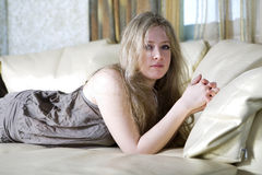 Muchacha adolescente rubia seria que miente en cama Fotografía de archivo