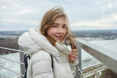 Muchacha adolescente rubia sonriente adorable joven que se divierte en la plataforma de observación con vistas al cielo nublado d Foto de archivo libre de regalías