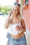 Muchacha adolescente rubia sonriente que habla en el teléfono Imagen de archivo