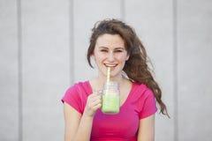 Muchacha adolescente sana joven que bebe un jugo alimenticio verde con Imagen de archivo