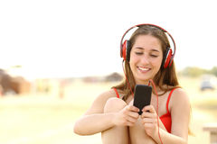 Muchacha adolescente sincera que escucha la música de un teléfono elegante Imagen de archivo libre de regalías