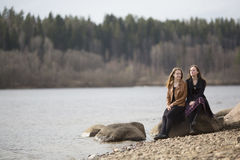 Muchacha adolescente soñadora y hermosa que se sienta en las piedras por el río El caminar Fotografía de archivo
