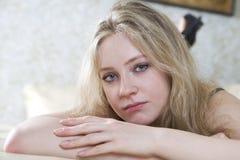 Muchacha adolescente sola rubia que miente en cama Imagen de archivo libre de regalías