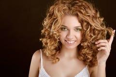 Muchacha adolescente sonriente atractiva con el pelo rizado Fotos de archivo