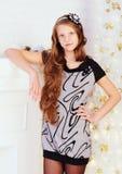 Muchacha adolescente sonriente bastante de pelo largo elegante en vestido en interio Foto de archivo