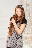 Muchacha adolescente sonriente bastante de pelo largo elegante en vestido en interio Imágenes de archivo libres de regalías