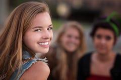 Muchacha adolescente sonriente con dos amigos Fotografía de archivo