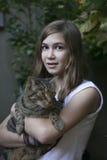 Muchacha adolescente sonriente con el gato en jardín Foto de archivo