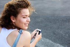 Muchacha adolescente sonriente con el teléfono elegante afuera Fotos de archivo libres de regalías