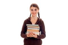 Muchacha adolescente sonriente con la derecha y los controles del smortit de las coletas muchos libros Fotografía de archivo