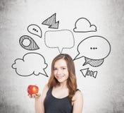 Muchacha adolescente sonriente con la manzana, charla Fotos de archivo libres de regalías
