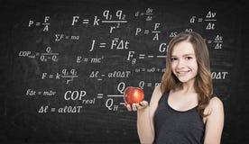 Muchacha adolescente sonriente con la manzana y fórmulas Imagenes de archivo