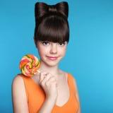 Muchacha adolescente sonriente con la piruleta colorida Brun divertido atractivo Fotos de archivo libres de regalías