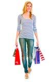 Muchacha adolescente sonriente con los bolsos de compras que hacen el paso de progresión Imagen de archivo