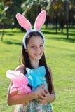 Muchacha adolescente sonriente con los oídos de conejo que sostienen los huevos de chocolate de Pascua Foto de archivo