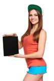 Muchacha adolescente sonriente de la cadera que muestra la pantalla digital en blanco negra de la tableta Foto de archivo