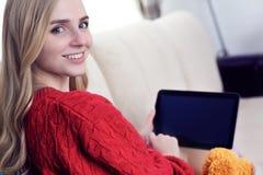 Muchacha adolescente sonriente de los jóvenes en casa que se relaja en correo electrónico de la lectura del sofá del sofá en la t Imágenes de archivo libres de regalías