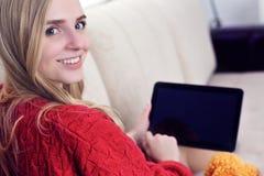 Muchacha adolescente sonriente de los jóvenes en casa que se relaja en correo electrónico de la lectura del sofá del sofá en la t Fotos de archivo