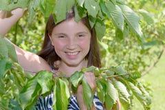 Muchacha adolescente sonriente de los jóvenes hermosos, en el follaje Imagen de archivo