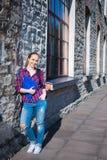 Muchacha adolescente sonriente del estudiante con la mochila que se coloca en la calle Foto de archivo libre de regalías